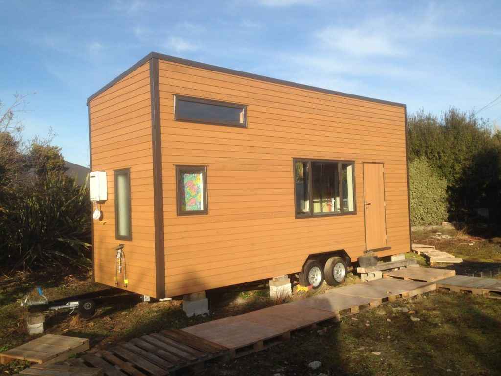 The tiny house in its current glory. Clad fully in Cedar with solid custom cedar door. Note the califont on the end.